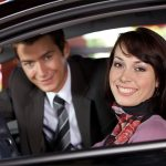 Couples sitting in a used car at showroom